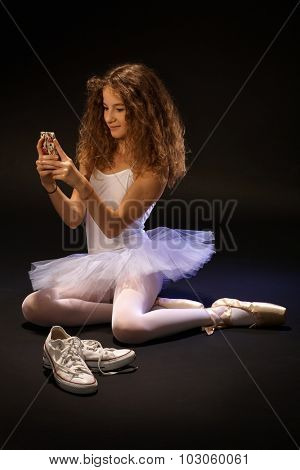 Pretty ballet student using mobilephone, sitting on floor, smiling.