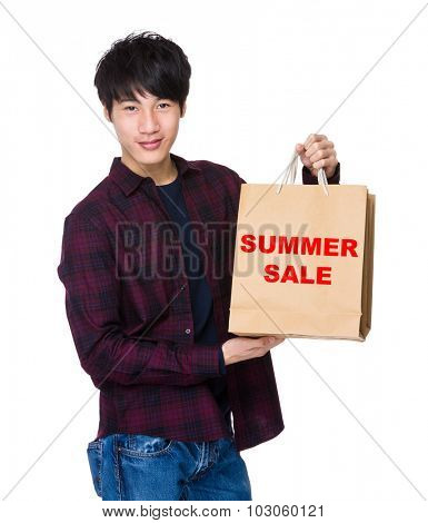Young Man hold with shopping bag for showing phrase of summer sale