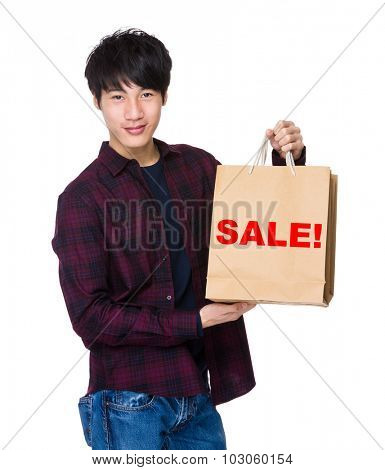 Young Man hold with shopping bag for showing a word sale!