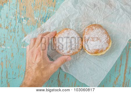 Hand Reaches For Sweet Sugary Donut On Rustic Table