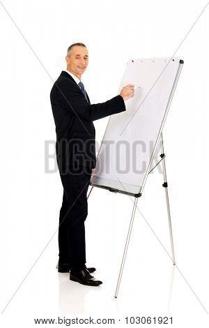 Mature businessman writing on a flipchart
