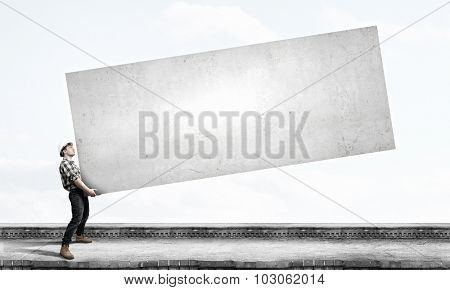 Young builder man in hardhat carrying stone wall banner