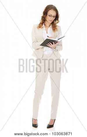 Businesswoman in eyewear writing in a note.
