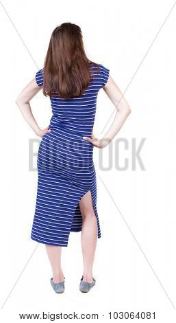 back view standing young beautiful  woman. girl  watching. Rear view people collection.  backside view person.  Isolated over white background. A girl in a long blue dress put her hands on her waist