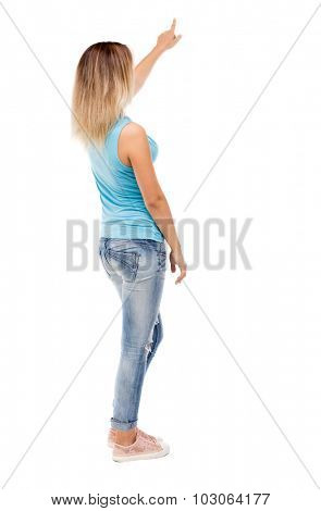 Back view of  pointing woman. beautiful girl. Rear view people collection.  backside view person. Isolated over white background. girl in jeans and a blue t-shirt standing and shows his left hand up.