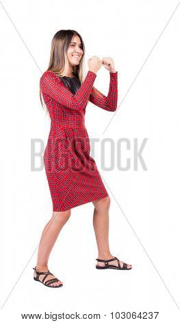 skinny woman funny fights waving his arms and legs. Rear view people collection.  backside view of person.  Isolated over white background. girl in red plaid dress smiling to become a boxing stance.