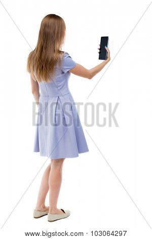 back view of standing young beautiful  girl with tablet computer in the hands of.  backside view of person.  Isolated over white background. The girl in a blue dress stands sideways and looks at plate