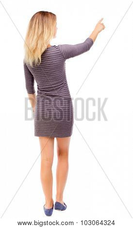 Back view of  pointing woman. beautiful girl. Rear view people collection.  backside view of person.  Isolated over white background. Girl in purple dress shows a finger to the right.