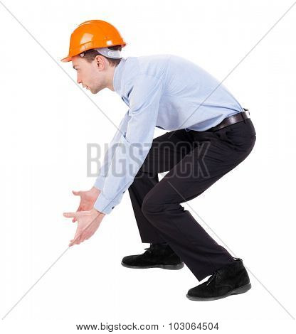 Backview of an engineer in construction helmet. Standing young guy. Rear view people collection.  backside view of person.  Isolated over white background. Construction worker picks up something.