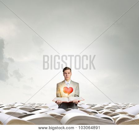 Young man in pile of books with one in hand