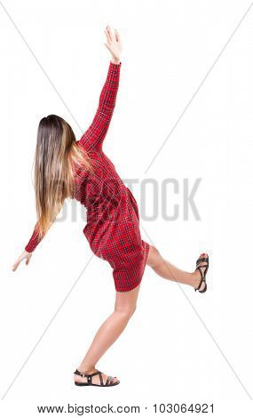 Balancing young woman.  or dodge falling woman. Rear view people collection.  backside view of person.  Isolated over white background. The girl in red plaid dress balances trying not to fall.