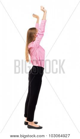 Back view of  joyful woman celebrating victory hands up. Rear view people collection. backside view person. Isolated over white background. A girl in pink shirt standing sideways holding up both hands