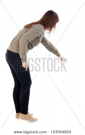 Back view of  pointing woman. beautiful girl. Rear view people collection.  backside view of person.  Isolated over white background.  girl in gray sweater shows finger his right hand down somewhere.