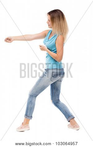 back view standing girl pulling a rope from the top or cling to something. girl  watching. Rear view people collection. Isolated over white background. girl in jeans and a blue shirt pulling the rope.
