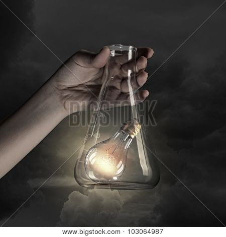 Hand holds flask with glass light bulb inside