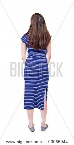 back view of standing young beautiful  woman.  girl  watching. Rear view people collection.  backside view of person.  Isolated over white background. A girl in a long blue dress looks up.