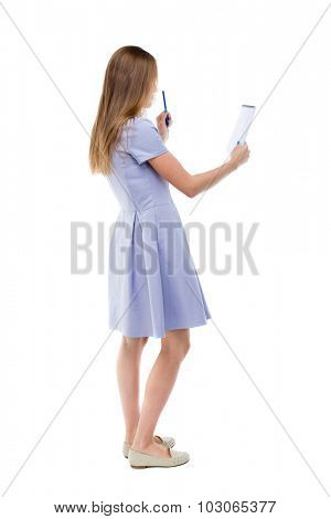 back view stands woman takes notes in notebook. girl watching. Rear view people collection. backside view person. Isolated over white background. girl in dress stands sideways and looks in notebook