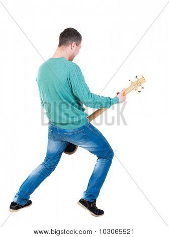 Back view of young man with guitar. Rock star with a musical instrument.  Rear view people collection.  backside view person.  Isolated over white background. Young bass player plays with enthusiasm