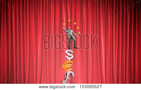 Young businessman balancing on currency signs and juggling with balls