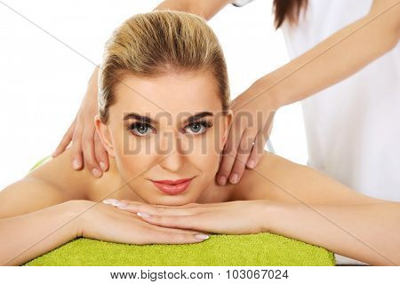 Young beautiful relaxed woman lying on a massage table and has massage.
