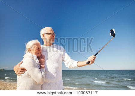 age, travel, tourism, technology and people concept - happy senior couple with smartphone on selfie stick taking picture on summer beach