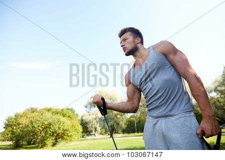 fitness, sport, exercising, training and lifestyle concept - young man exercising with expander in summer park