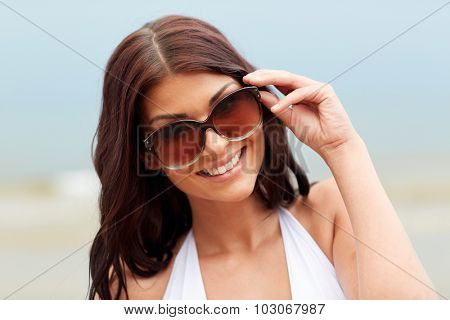 summer vacation, tourism, travel, holidays and people concept -face of smiling young woman with sunglasses on beach