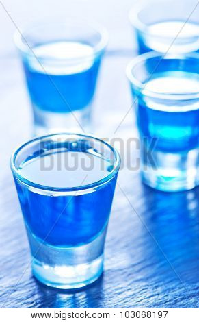 Blue Alcoholic Drink Into Small Glasses