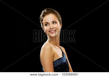 people, holidays and glamour concept - beautiful woman wearing dress and pearl earrings over black background