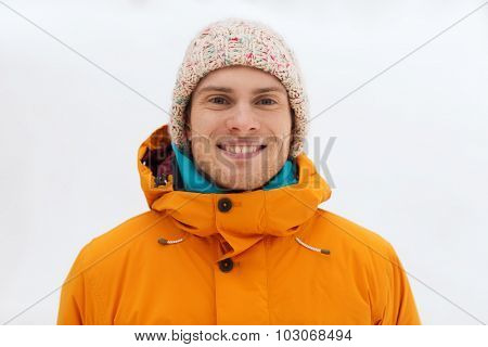 winter, leisure, clothing and people concept - happy teenage boy or young man in winter clothes outdoors