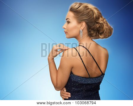 people, holidays, jewelry and glamour concept - beautiful woman with diamond earring over blue background