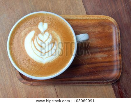 flat white coffee with latte art on wooden saucer and table