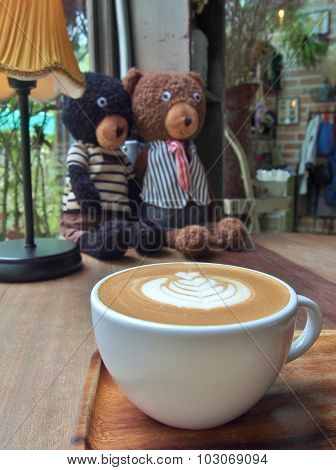 coffee with latte art and two bear dolls