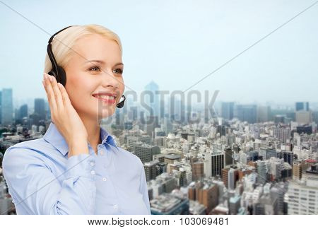 business, people, technology and communication concept - happy female helpline operator in headset over city background