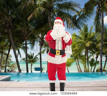 christmas, holidays, travel and people concept - man in costume of santa claus with bag making hush gesture over swimming pool on tropical beach background