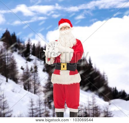 christmas, holidays and people concept - man in costume of santa claus with clock showing twelve pointing finger over snowy mountains background