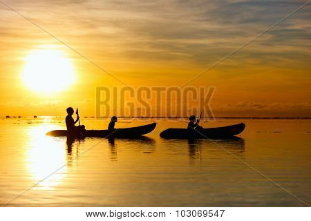 Silhouettes of family with kids paddling at tropical ocean at sunset