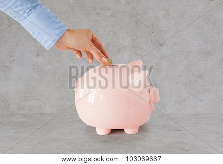 business, finance, investment, money saving and budget concept - close up of hand putting coin into piggy bank over gray concrete background
