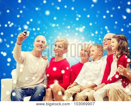 family, holidays, generation, christmas and people concept - smiling family with camera taking selfie and sitting on couch over blue snowy background