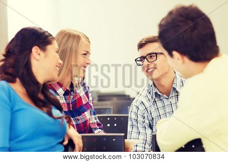 education, high school, teamwork and people concept - group of smiling students sitting and talking in lecture hall