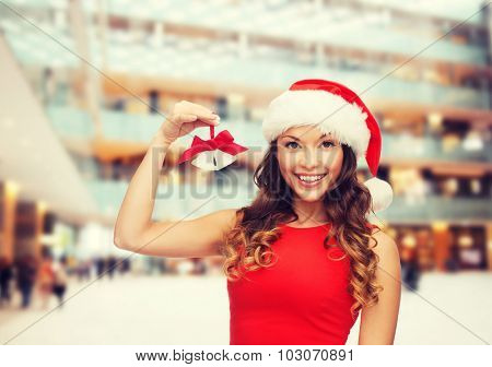 christmas, holidays, winter, happiness and people concept - smiling woman in santa helper hat with jingle bells over shopping center background