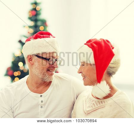 family, holidays, christmas, age and people concept - happy senior couple in santa helper hats sitting on sofa over living room and christmas tree background