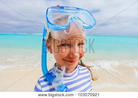 Wide angle photo of adorable little girl with snorkeling equipment at beach during summer vacation