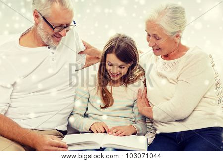family, generation, education and people concept - smiling grandfather, granddaughter and grandmother with book sitting on couch at home