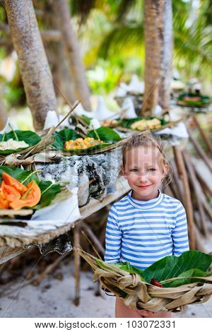 Little girl holding weaved plate with some local south pacific origin food served in giant shells