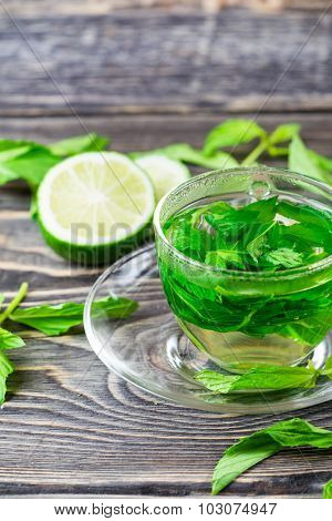 Glass cup of hot tea with fresh mint  on wooden background
