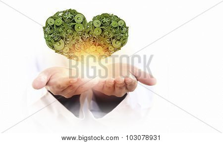 Male hands holding heart made of gears and cogs