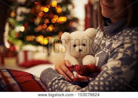 Young woman with teddy bear enjoying Christmas eve at home