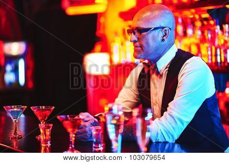 Bald barman standing by counter with drinks in night club