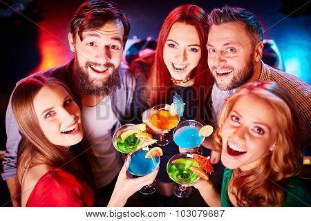 Ecstatic guys and girls toasting at party and looking at camera